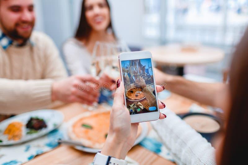 Vrouwelijke hand die foto van groep mensen maken die avondmaal in koffie hebben royalty-vrije stock fotografie