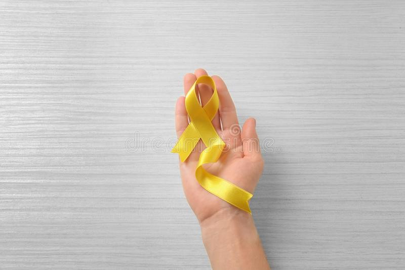 Vrouwelijke hand die geel lint op lichte achtergrond houden Kankerconcept royalty-vrije stock fotografie