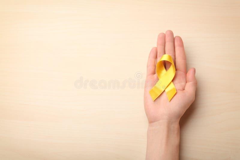Vrouwelijke hand die geel lint op lichte achtergrond houden Kankerconcept stock afbeeldingen