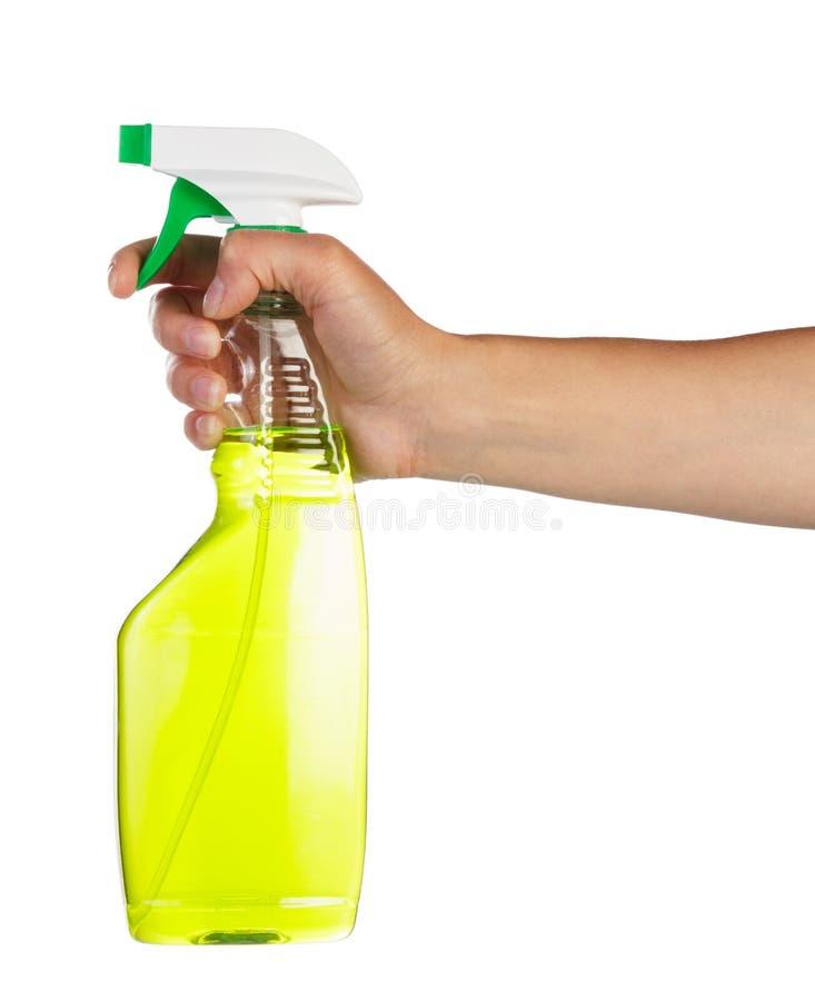 Vrouwelijke hand die groene nevelfles voor geïsoleerd schoonmaken houden stock fotografie