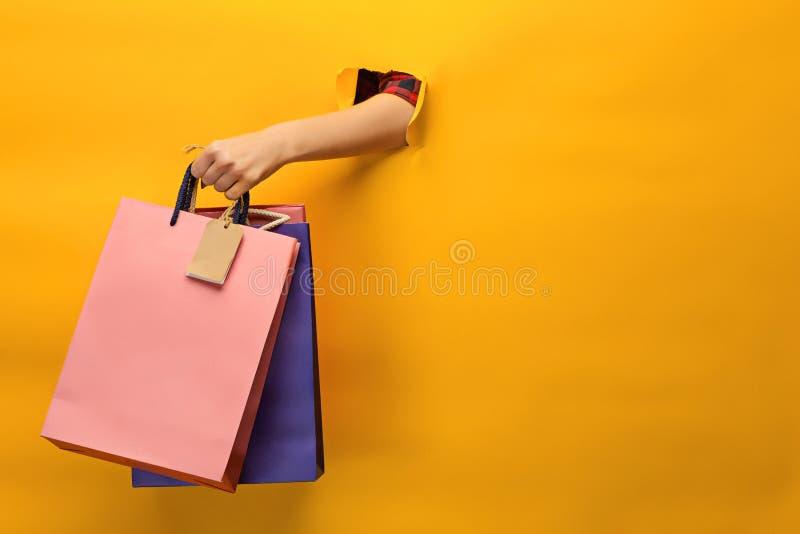 Vrouwelijke hand die heldere het winkelen zakken houdt royalty-vrije stock afbeeldingen