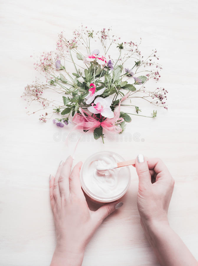 Vrouwelijke hand die kruidenroom met organische kruiden en bloemen maken op witte houten achtergrond, hoogste mening bundelen Org royalty-vrije stock afbeelding