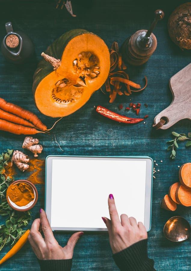 Vrouwelijke hand die met vinger op tabletpc richten met spot op het scherm op donkere keukenlijst met oranje kokende ingrediënten stock fotografie