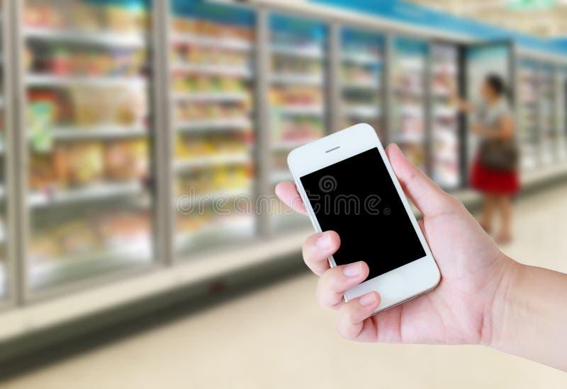 Vrouwelijke hand die mobiele slimme telefoon op Supermarkt houden royalty-vrije stock foto's