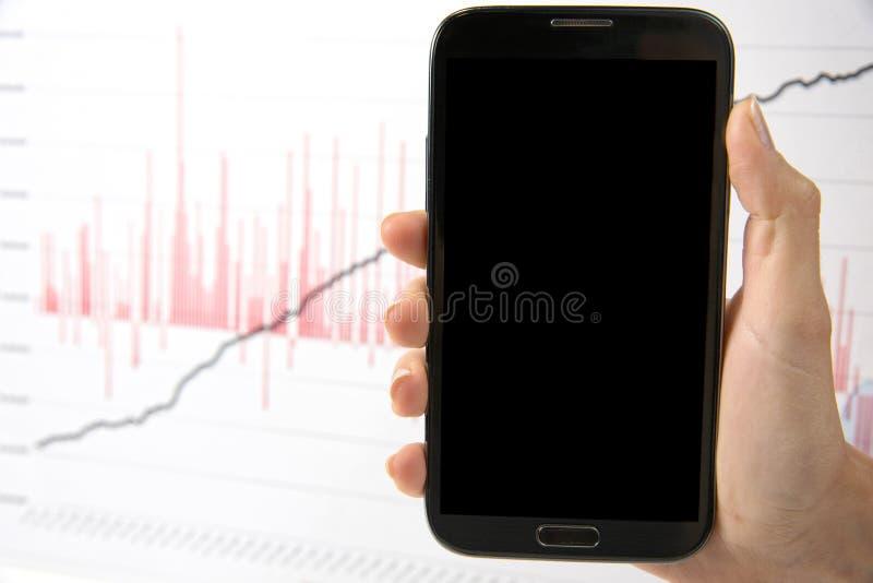 Vrouwelijke hand die mobiele telefoon over diagram houden royalty-vrije stock afbeeldingen