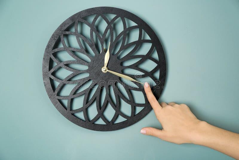 Vrouwelijke hand die op klok tegen kleurenachtergrond richten Het Concept van het tijdbeheer stock afbeeldingen