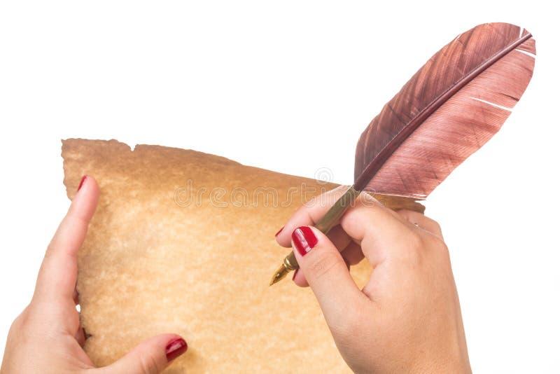 Vrouwelijke hand die op oude die document rol en vulpen met veerschacht schrijven op witte achtergrond wordt geïsoleerd stock foto