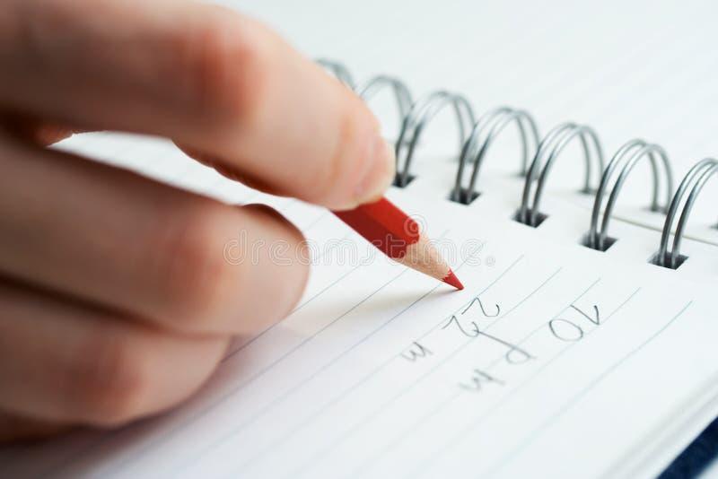 Vrouwelijke hand die op pagina schrijft. stock afbeeldingen