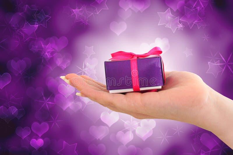 Vrouwelijke hand die purpere gift houdt stock afbeelding