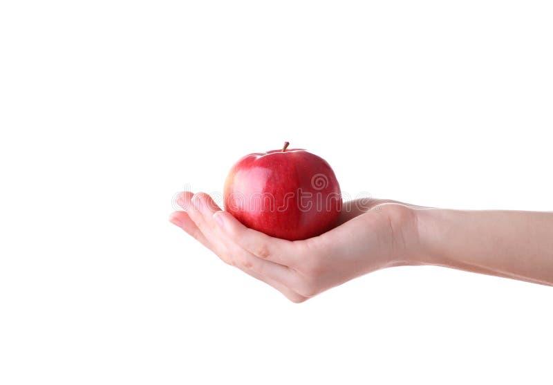 Vrouwelijke hand die rode die appel houden op witte achtergrond wordt geïsoleerd royalty-vrije stock afbeeldingen