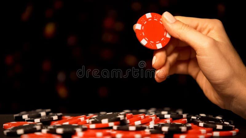 Vrouwelijke hand die rode spaander nemen, die geluk in het gokken, casino het winnen weddenschappen aantrekken stock afbeeldingen
