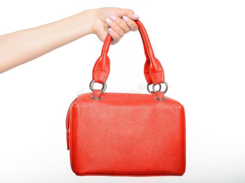 Vrouwelijke hand die rode zak geïsoleerd houden stock foto's