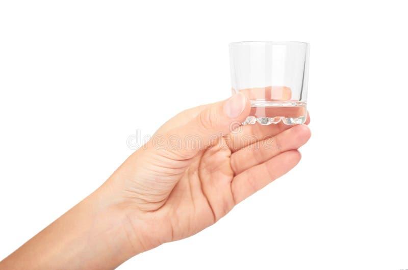 Vrouwelijke hand die transparante glaskop houden Geïsoleerdj op witte achtergrond royalty-vrije stock afbeelding