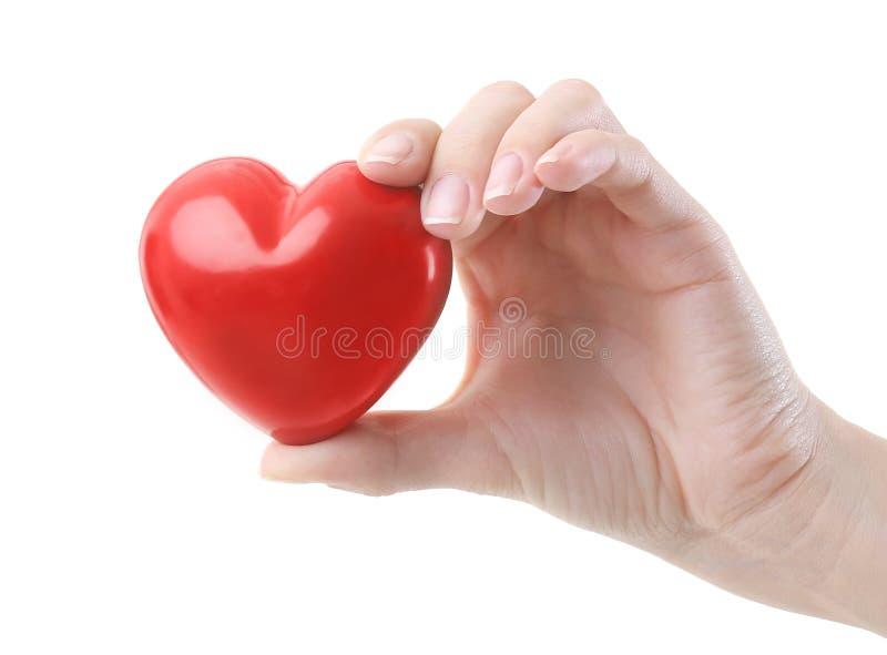 Vrouwelijke hand die weinig ceramisch hart houden stock afbeeldingen