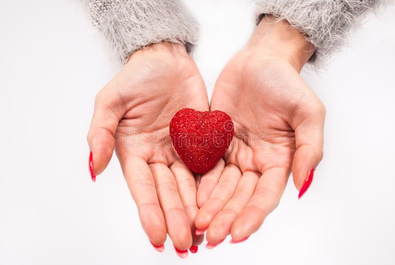 Vrouwelijke hand die weinig hart op witte achtergrond rood houden stock afbeeldingen