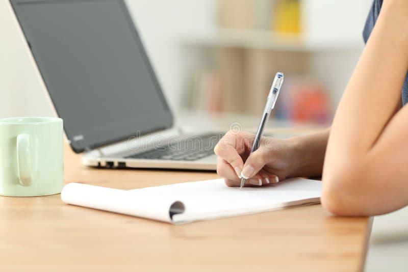Vrouwelijke hand het schrijven nota's in een notitieboekje op een bureau royalty-vrije stock foto