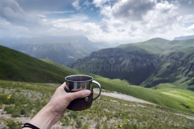 Vrouwelijke hand met een kop thee op een achtergrond van bergen royalty-vrije stock fotografie