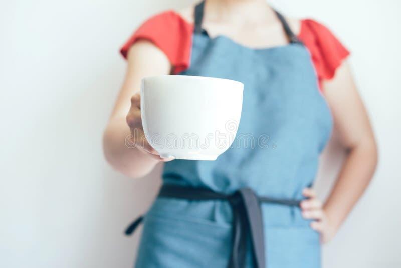 Vrouwelijke hand met een witte mokclose-up stock foto