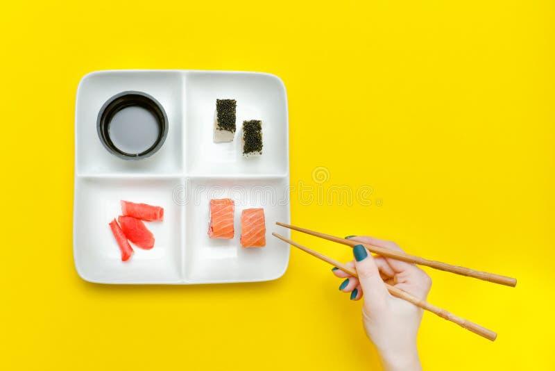 Vrouwelijke hand met eetstokjes en plaat met sushi op gele bac royalty-vrije stock foto's