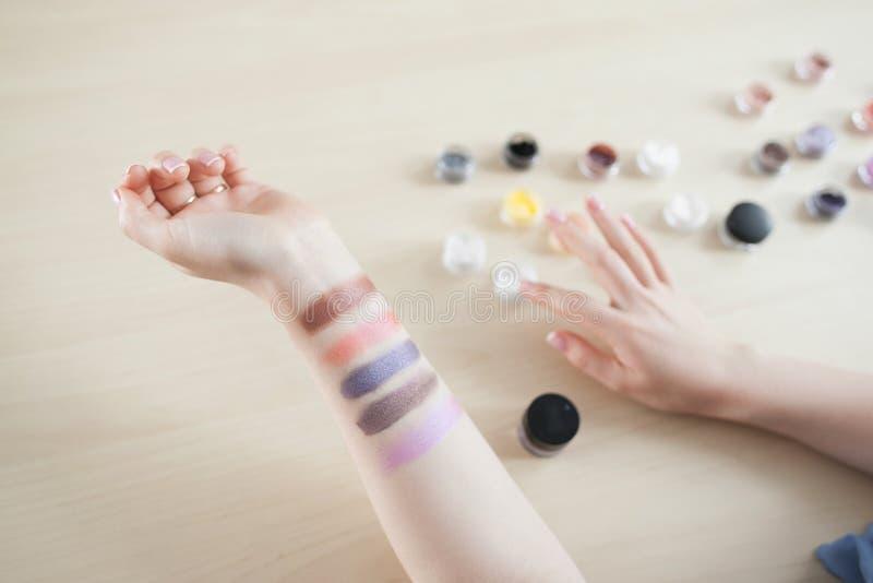 Vrouwelijke hand met kleurrijke oogschaduwvlekken stock fotografie