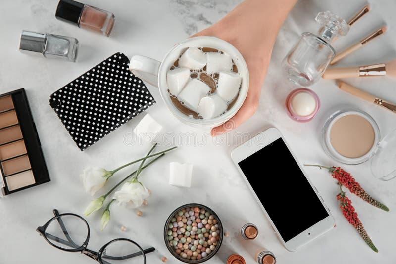 Vrouwelijke hand met kop koffie, mobiele telefoon en schoonheidsmiddelen op lijst stock afbeeldingen