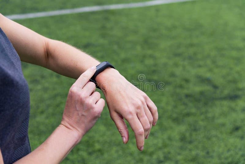 Vrouwelijke hand met slim horloge op de groene openluchtachtergrond van het sportenstadion royalty-vrije stock afbeeldingen