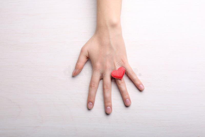 Vrouwelijke hand met weinig hart op vinger op lichte backgrou stock fotografie