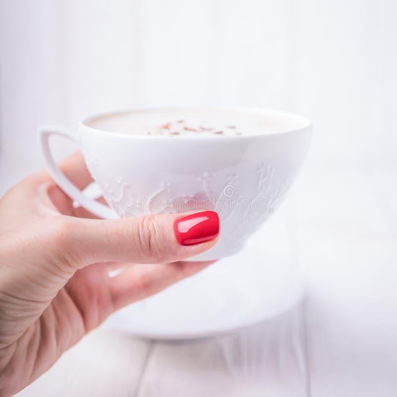 Vrouwelijke hand met witte porselein kop koffie cappuccino met kaneel Manicure met rood nagellak Kopieerruimte stock afbeeldingen