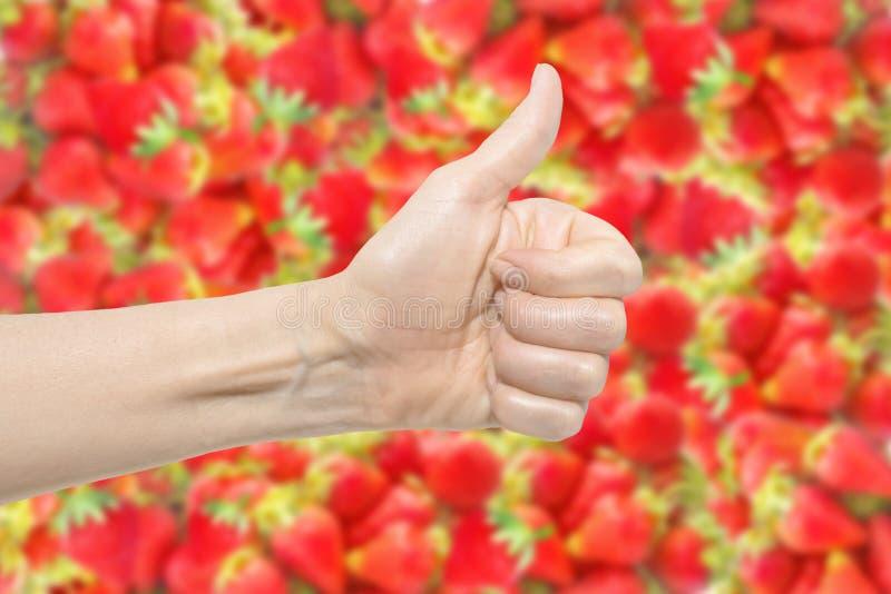 Vrouwelijke hand op heldere rode verse vage aardbeiachtergrond De duim omhoog Het concept van de gewassenkwaliteit Symbolen en ge stock fotografie