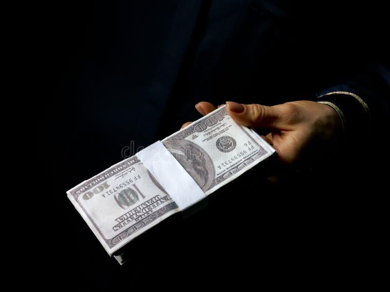 Vrouwelijke hand op zwart tonend pak dollars stock afbeeldingen