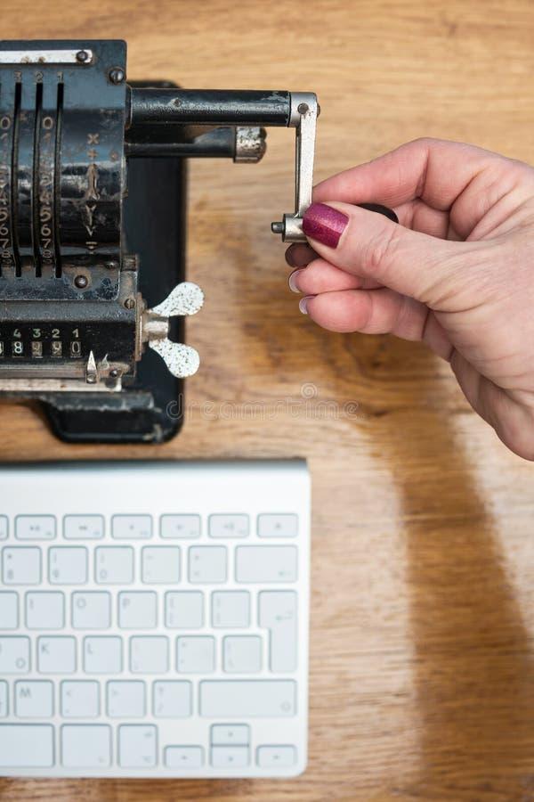 Vrouwelijke hand turninghandle van een rekenmachine royalty-vrije stock foto
