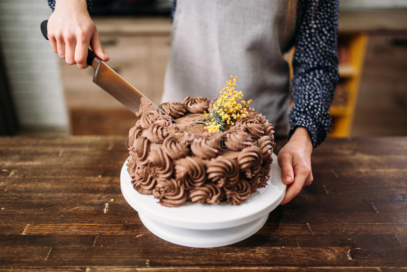 Vrouwelijke handen die chocoladecake met een mes snijden royalty-vrije stock fotografie