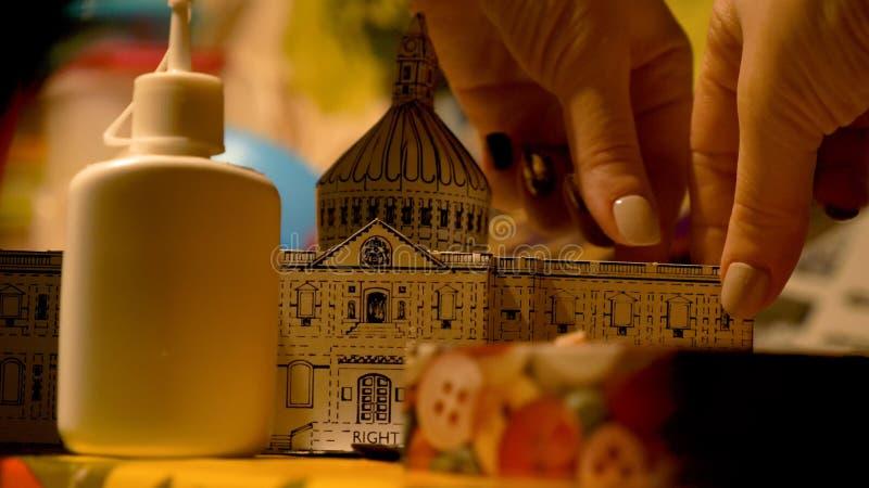 Vrouwelijke handen die de bouwmodel thuis assembleren van Heilige Pauls Cathedral Hobby en vrije tijd stock afbeelding