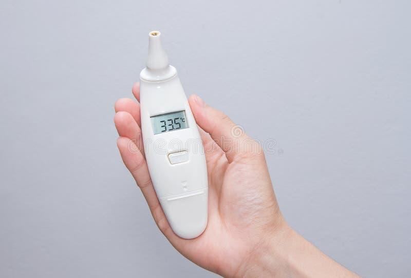 Vrouwelijke handen die digitale thermometer houden royalty-vrije stock afbeeldingen