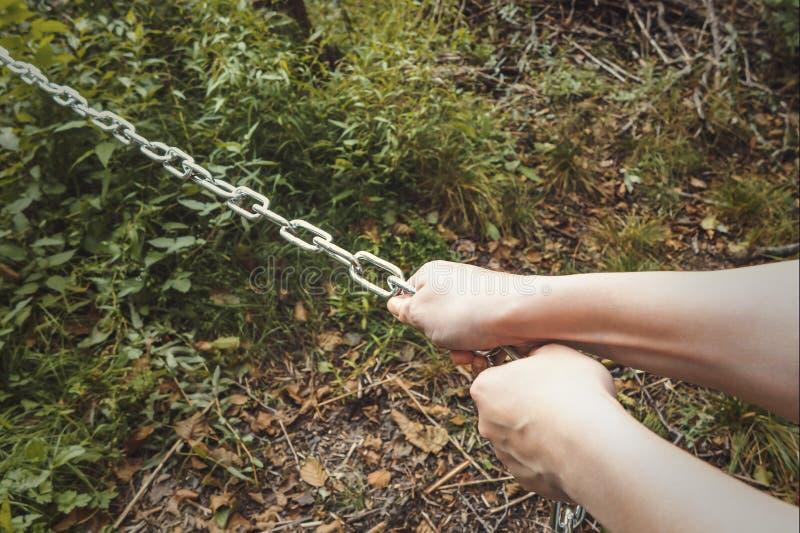 Vrouwelijke handen die een dikke metaalketting trekken - het concept het harde werk, ondraaglijke last royalty-vrije stock afbeeldingen