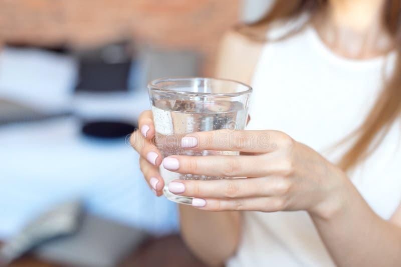 Vrouwelijke handen die een duidelijk glas water houden Een glas schoon mineraalwater in handen, gezonde drank stock fotografie