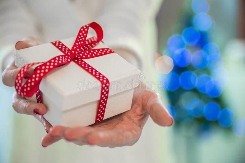 Vrouwelijke handen die een huidige doos, portret van jonge glimlachende vrouw in verfraaide woonkamer met giften en Kerstboom hou royalty-vrije stock afbeelding