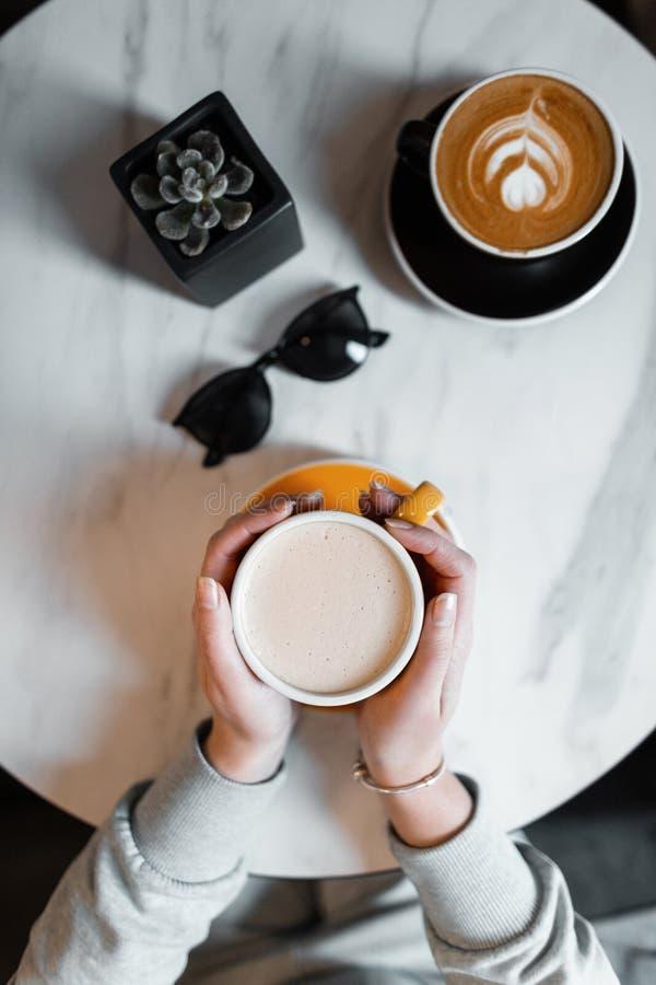 Vrouwelijke handen die een kop met hete koffie in de koffie houden De jonge vrouw zit in de ochtend binnen Hoogste mening van de  royalty-vrije stock afbeeldingen