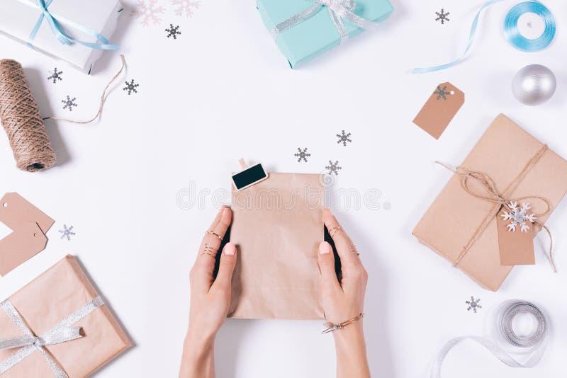 Vrouwelijke handen die een pakket met een gift onder Kerstmisdecor houden royalty-vrije stock afbeeldingen