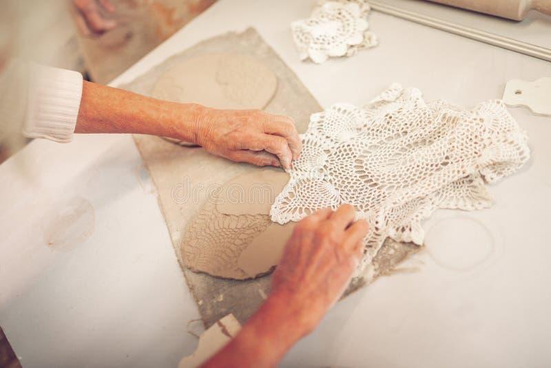 Vrouwelijke handen die een wit gehaakt servet houden stock fotografie