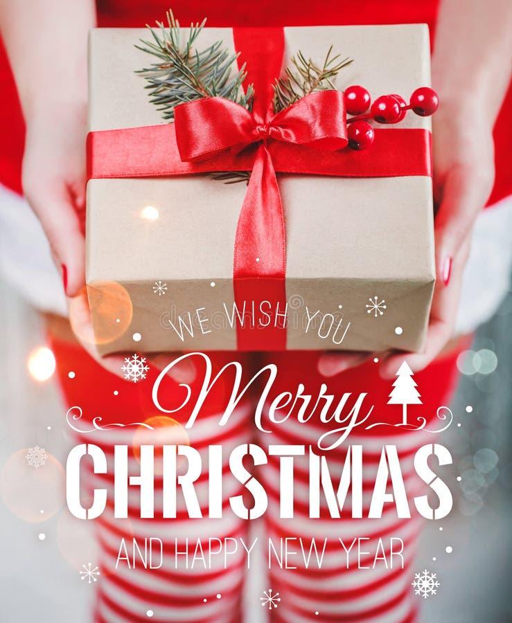 Vrouwelijke handen die giftdoos met rood lint en Vrolijk Kerstmis en Nieuwjaar typografisch op glanzende Kerstmisachtergrond houd royalty-vrije stock afbeeldingen