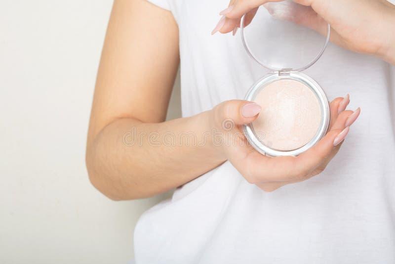 Vrouwelijke handen die het benadrukken van gedrukt poeder met een rookwolk over een witte achtergrond houden Ruimte voor tekst royalty-vrije stock foto