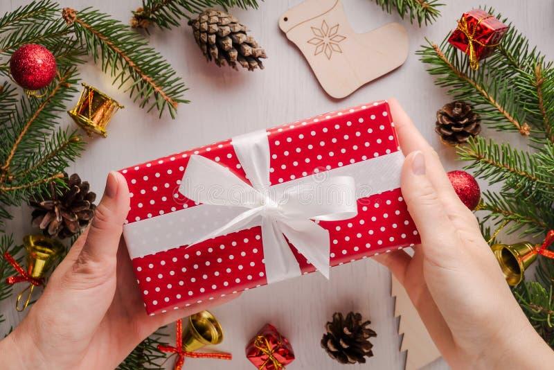 Vrouwelijke handen die Kerstmisgift houden die in rood document wordt verpakt royalty-vrije stock afbeelding