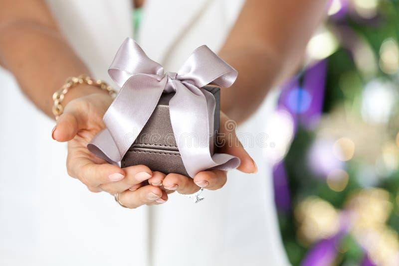 Vrouwelijke handen die kleine elegante gift met lint houden royalty-vrije stock fotografie
