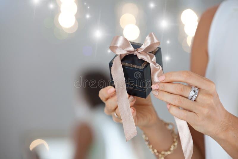 Vrouwelijke handen die kleine elegante gift met lint houden stock afbeeldingen