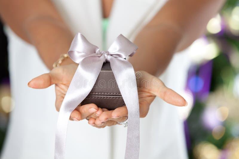 Vrouwelijke handen die kleine elegante gift met lint houden stock fotografie