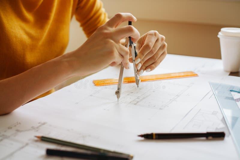 Vrouwelijke handen die kompas voor een technische tekening gebruiken royalty-vrije stock afbeeldingen