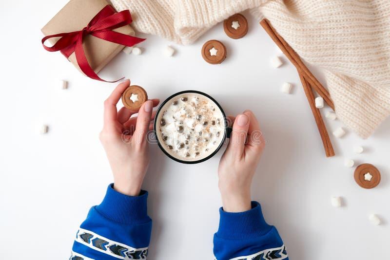 Vrouwelijke handen die kop van hete chocolade met heemst houden Kerstmisdrank, smakelijke koekjes, giftdoos op witte achtergrond  stock foto