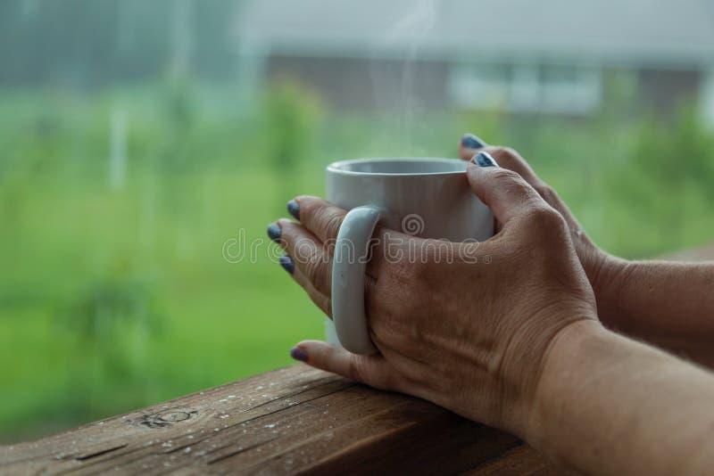 Vrouwelijke handen die kop van koffie in de regenachtige dag houden royalty-vrije stock fotografie