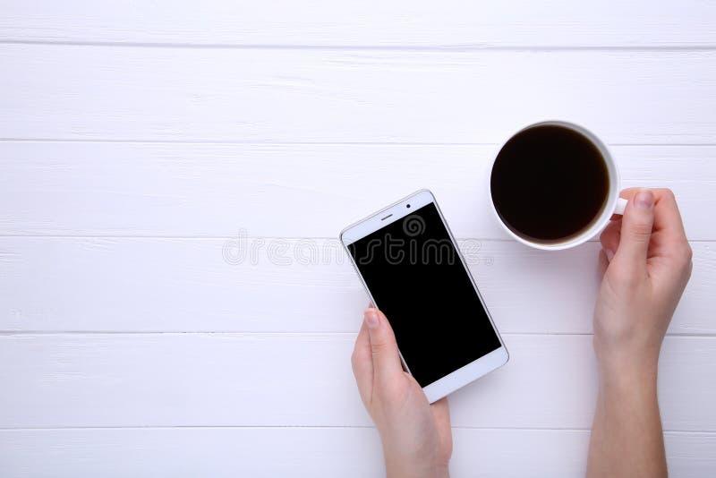 Vrouwelijke handen die kop van koffie en smartphone op witte houten achtergrond houden stock foto